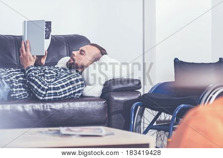 Reading amazing story. Young positive optimistic invalid lying on the couch next to the wheelchair at home and having rest while reading book