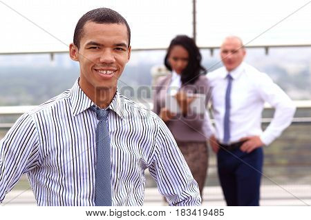 a young handsome black businessman is standing outside of a business building, confidently looking forward.