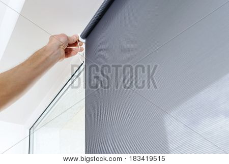 Man's hand is puting a roller blind to a window.