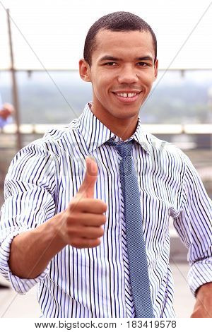 Smiling african businessman with thumbs up outdoors