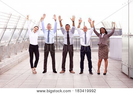 Business winners. Full length of group of happy young people in formal wear celebrating, gesturing, keeping arms raised and expressing positivity.