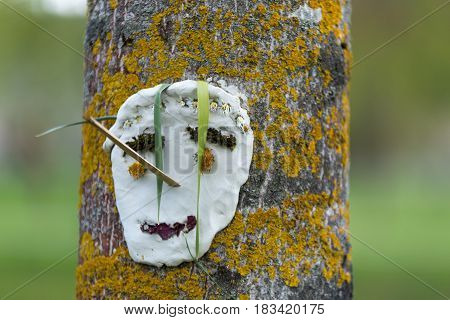 Handmade Face Sculpture Smiling Made By Children Hanged On A Tree. Face Made With Wood Sticks, Flowe