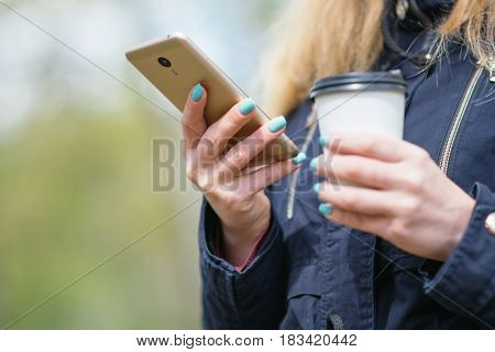 A girl is walking in the morning in a park with a smartphone and coffee