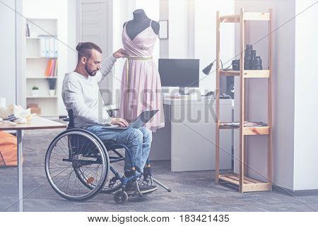 Enjoying my inspirational job. Talented hardworking involved handicap sitting on the wheelchair in the studio and working while using gadget and taking measurements for clothes