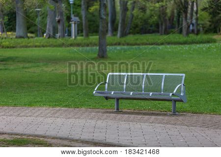 Steel Modern Bench On A Park With Green Grass, Trees And A Pavement Sidewalk Path.