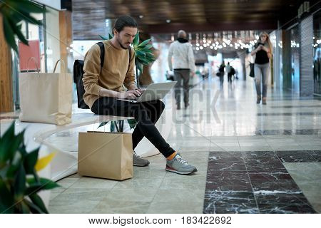 Student after buy clothes talk with friends in social network by laptop in shopping center. Man working during weekend walking. Immediate job for a freelance worker. Copy space for advertising sales.