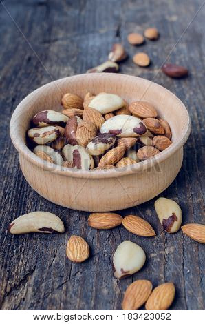 Nuts mix of almonds and Brazil nuts in wooden bowl on old rustic background. Healthy edible seeds food ingredient on the table.