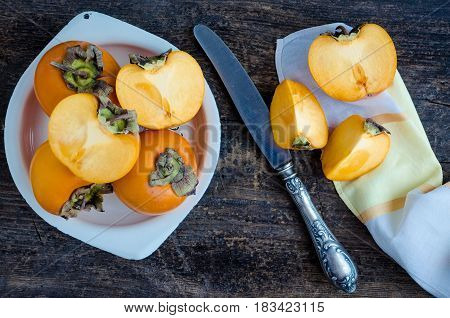 Slice of ripe delicious fresh persimmon kaki fruit in white metal plate with knife and napkin on old wooden table. Top view.