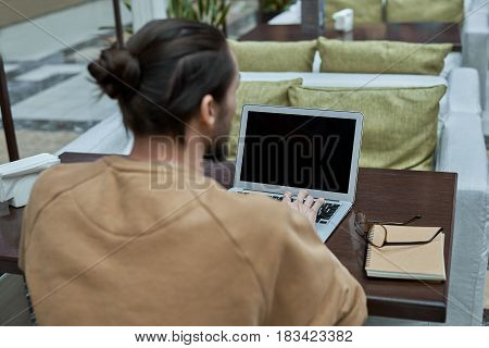 Back view of Stylish man with long hair sit at mock up laptop in cafe and check email and social network after shopping in emporium. Live with internet technology.