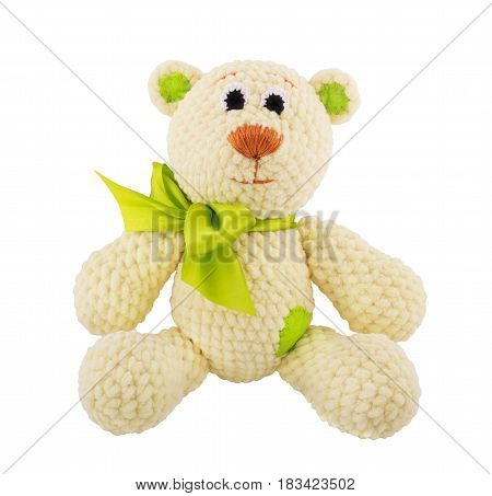 Plush knitted teddy bear with a green bow. Soft toy. Handmade. Isolated on white.
