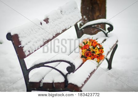 Bouquet And Lilies On A Bench In The Snow In The Winter