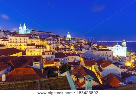 Panoramic view of Alfama, the oldest district of the Old Town, with Monastery of Sao Vicente de Fora, Church of Saint Stephen and National Pantheon during evening blue hour, Lisbon, Portugal