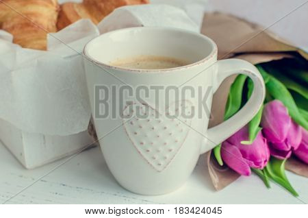 Cup of coffee with bouquet of pink tulips and croissants on white shabby chic table. Valentines Mothers Womens Day morning concept. Valentine's day breakfast.
