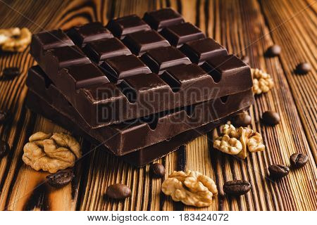 Three pieces of bitter dark chocolate bar walnut core and coffee bean on wooden background close-up view.