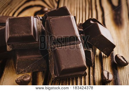 Pieces of bitter dark chocolate cubes on heap and coffee bean on wooden background close-up view.
