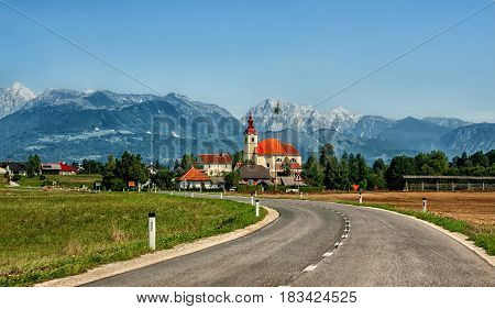 The European landscape where the road leads to the Church building on a background of mountains of Slovenia in Sunny cloudless day