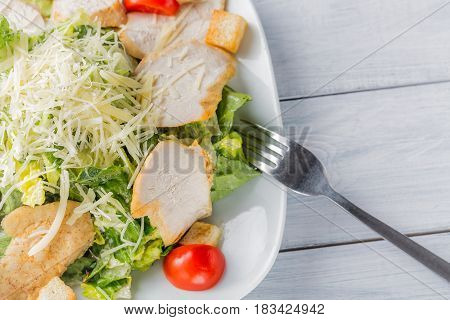 Healthy green organic caesar salad close up on white plate and fork.