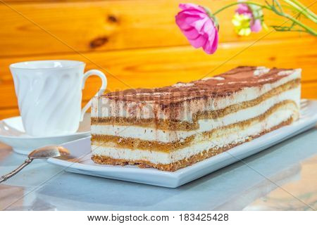 Delicious cake Tiramisu. The background is cup with tea and flowers. Professional bakery