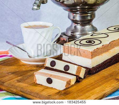 Gorgeous holiday cake Three-colate. The background is shiny samovar and porcelain cup with tea. Professional bakery. Three-layered chocolate cake decorated with chocolate patterns