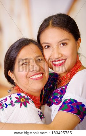 Beautiful portrait of mother with daughter, both wearing traditional andean clothes and matching necklaces, posing embracing happily.