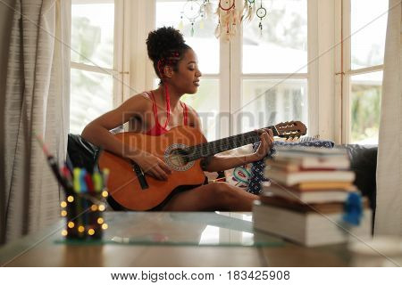 Mixed Race Girl Singing And Playing Classic Guitar At Home