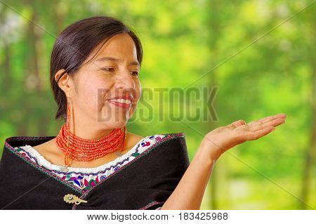 Closeup beautiful hispanic woman wearing traditional andean white blouse with colorful decoration around neck, black poncho, matching red necklace and ear, posing happily for camera, garden background.