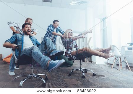 Override me. Cheeful content smiling colleagues riding in office chairs and smiling while having a break