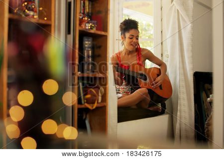 Black Woman Singing And Playing Guitar At Home