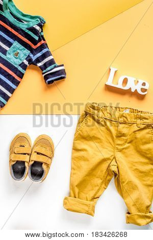 toys and clothes collection for child room on white and yellow table background top view