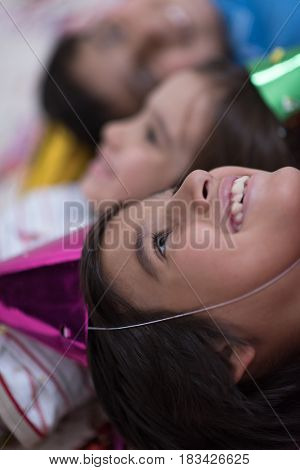 Happy kids celebrating party with blowing confetti while lying on the floor