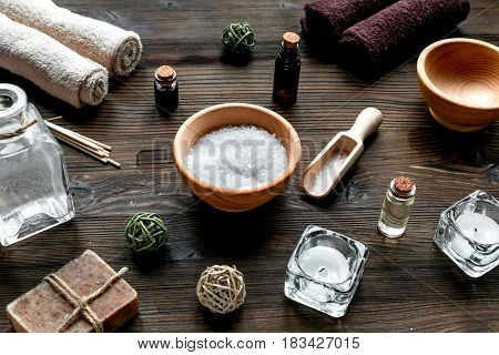 spa cosmetics set with soap, salt, oil, towels, candles on wooden desk background