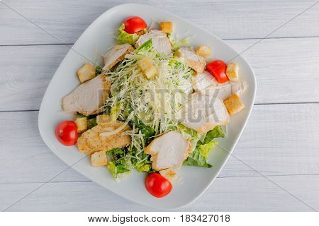 Healthy green organic caesar salad with cheese on white plate and wooden table. Top view.