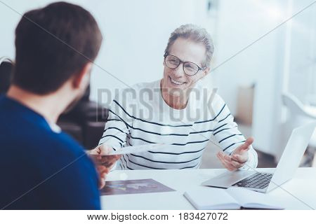Business deal. Positive cheerful colleagues sittign at the table and working in the office while discussing business contract