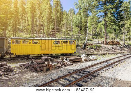 Steam train carriage on tracks in forest
