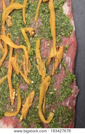 Raw flank steak being prepared with peppers cheese olives parsley and garlic ready to be rolled and baked