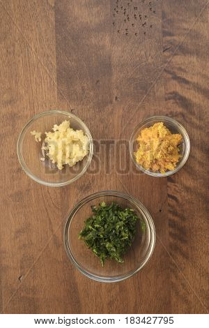 Garlic parsley and orange rind in measured bowls for a food dish preparation
