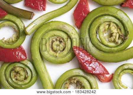 Fiddlehead Ferns and red pepper pieces layed out on a white ceramic plate