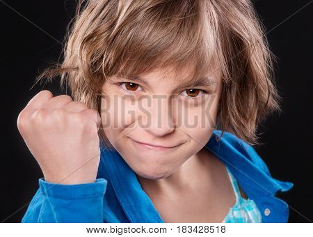 Close up emotional portrait of caucasian angry child. Beautiful severe teenage girl shakes her fist, against  black background. Negative human emotions facial expression feelings attitude.