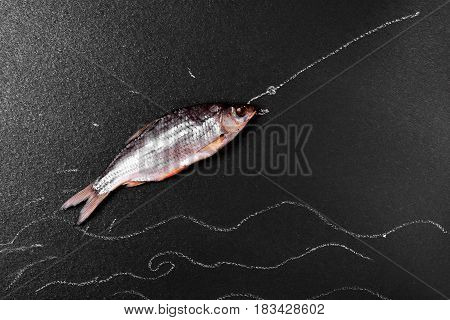 Fish ram on a black surface painted sea and hook