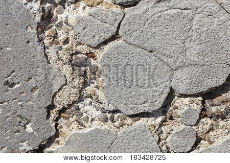 Old worn concrete wall cracking and pitted away