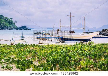 Beautiful banca boats on Nacpan beach on sunny day. El Nido, Palawan, Philippines.