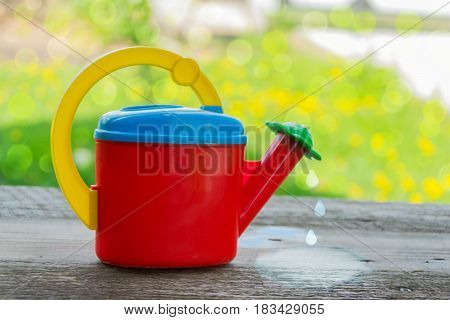 Watering cans for irrigation children's plastic on a wooden background with water drops on a Sunny day.