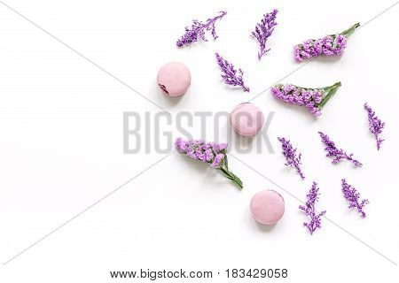 macaroons and purple flowers for light breakfast on white desk background top view mockup