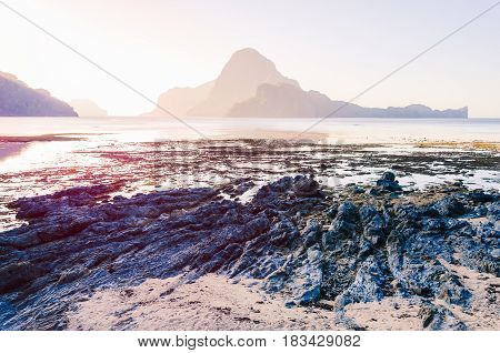 Low tide with Rocks in front and on sunrise and amazing shape of Cadlao Island in background, El-Nido, Palawan, Philippines.