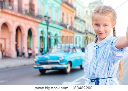 Tourist girl in popular area in Havana, Cuba. Young woman traveler smiling