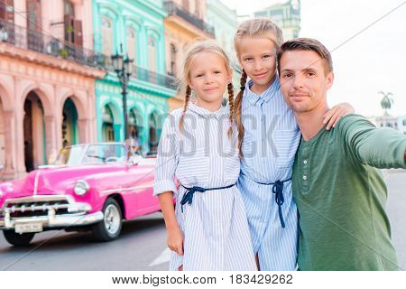 Tourist girls and father in popular area in Havana, Cuba. Young woman traveler smiling