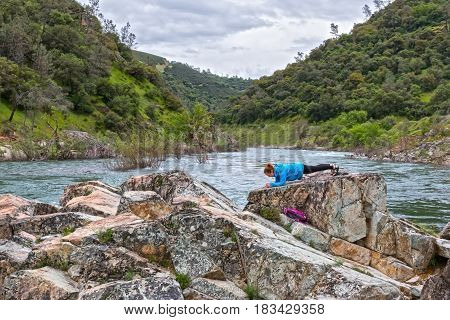 Young Girl Doing a Plank on Rocks Near Fast River