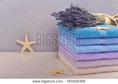 Stack of colorful bath towels on light background. Pastel colors cotton towels. Hygiene fabricspa and textile concept
