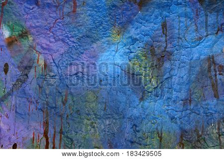 Textured abstract multicolor background. Close up. Dripping paint on roughgrunge plastered surface. Dirty old wall with different vivid colors : blueblack and beige