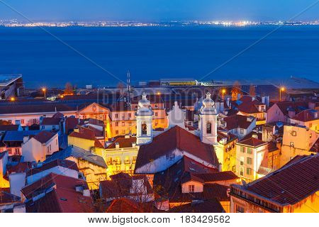 Panoramic view of Alfama, the oldest district of the Old Town, with Church of Saint Michael and Tejo river during evening blue hour, Lisbon, Portugal